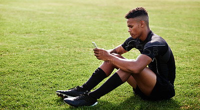 Buy stock photo Shot of a young man sitting on the field and using a smartphone at a rugby match
