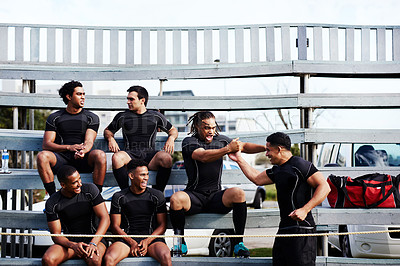 Buy stock photo Shot of a group of young men sitting on the benches together at a rugby game
