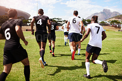 Buy stock photo Shot of a group of young rugby players running onto the field during a game