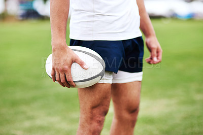 Buy stock photo Cropped shot of an unrecognisable man holding a rugby ball during a game