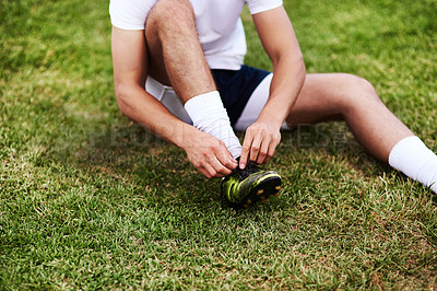 Buy stock photo Cropped shot of a man tying his shoelaces before playing a game of rugby