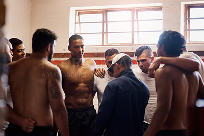 Buy stock photo Shot of a rugby coach addressing his team players in a locker room