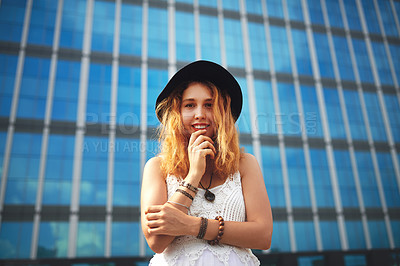 Buy stock photo Shot of a beautiful young woman posing outside against a glass building