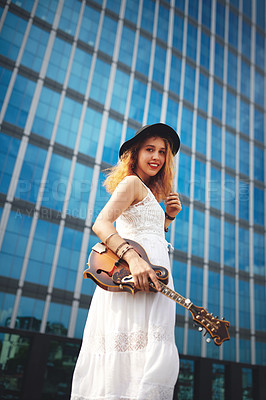 Buy stock photo Shot of a beautiful young woman out in the city with her guitar