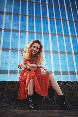 Buy stock photo Shot of a beautiful young woman sitting outside against a glass building