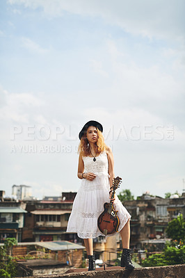 Buy stock photo Shot of a young woman out on a rooftop with her guitar