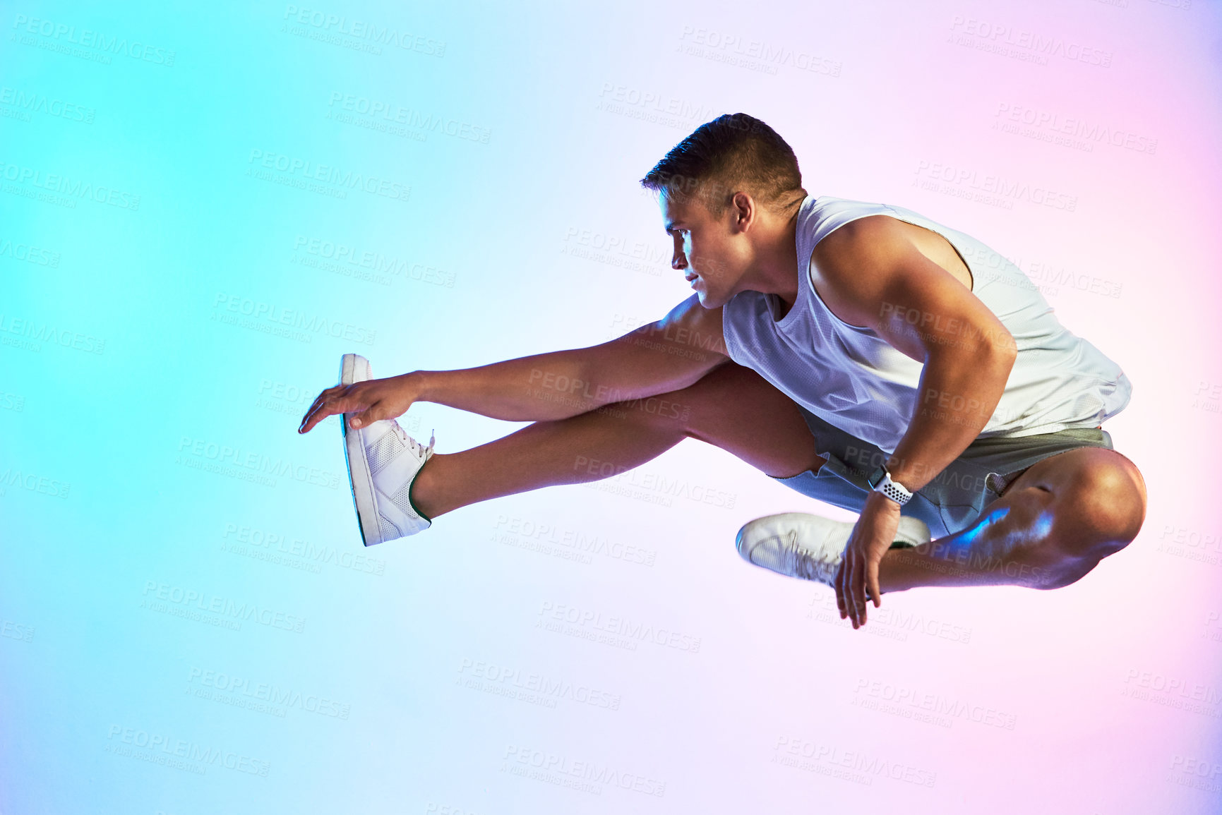 Buy stock photo Studio shot of a handsome young male athlete jumping against a multi-coloured background