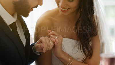 Buy stock photo Cropped shot of a newly married young couple linking their ring fingers at the wedding reception