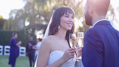 Buy stock photo Shot of a happy newly married young couple having champagne after getting married in a garden