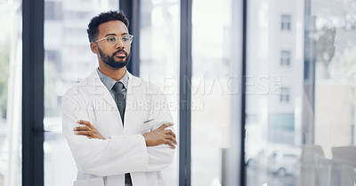 Buy stock photo Cropped shot of a male doctor standing with his arms crossed