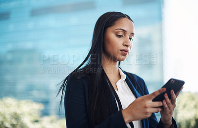 Buy stock photo Shot of a young businesswoman using a smartphone against a city background