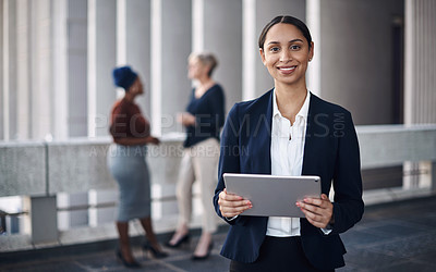 Buy stock photo Shot of a young businesswoman using a digital tablet against a city background