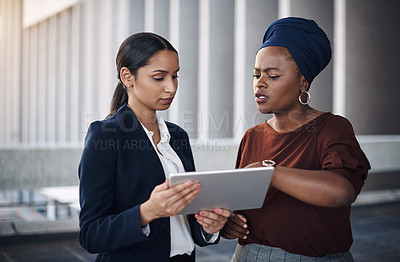 Buy stock photo Shot of two businesswomen using a digital tablet together against a city background