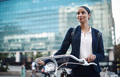 Buy stock photo Shot of a young businesswoman traveling with a bicycle through the city