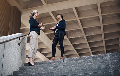 Buy stock photo Shot of two businesswomen having a discussion against a city background