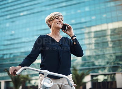 Buy stock photo Shot of a mature businesswoman using a smartphone while traveling with a bicycle through the city