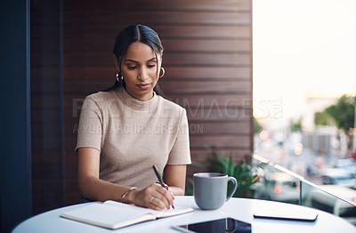 Buy stock photo Cropped shot of an attractive young businesswoman taking notes while working in her office