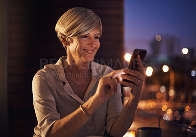 Buy stock photo Cropped shot of an attractive mature businesswoman sending a text while working late in her office