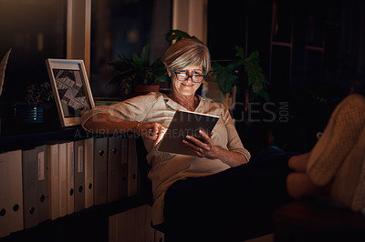 Buy stock photo Cropped shot of an attractive mature businesswoman looking relaxed while using her tablet late at night in the office