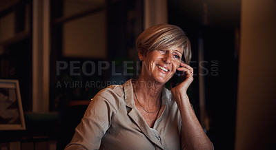 Buy stock photo Cropped shot of an attractive mature businesswoman working on her computer and making a phonecall in the office late at night