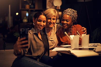 Buy stock photo Shot of a group of businesswomen taking selfies together in an office at night