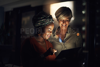 Buy stock photo Shot of two businesswomen using a digital tablet together in an office at night
