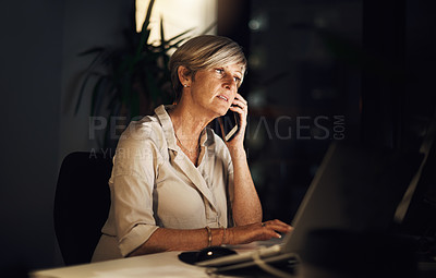 Buy stock photo Shot of a mature businesswoman talking on a cellphone while using a computer in an office at night