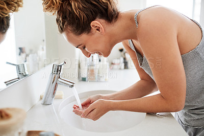 Buy stock photo Shot of a young woman washing her face at the bathroom sink in the morning