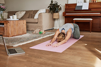 Buy stock photo Shot of a young woman practicing her yoga routine at home