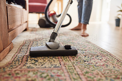 Buy stock photo Shot of a young woman vacuuming the living room at home
