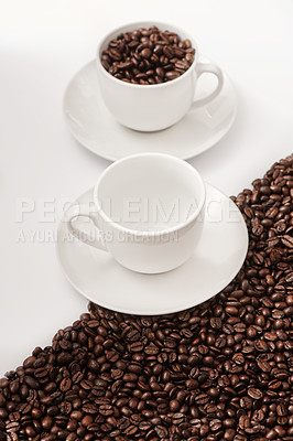 Buy stock photo Closeup shot of an empty cup and one filled with coffee beans against a half-and-half background