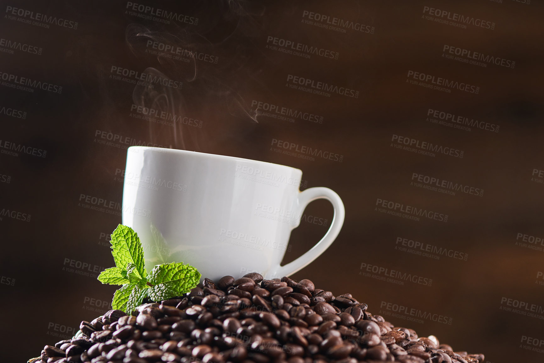 Buy stock photo Closeup shot of a mint leaf and a cup on a pile of coffee beans