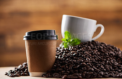 Buy stock photo Closeup shot of a paper cup on a surface, with a teacup and mint leaf resting on a pile of coffee beans in the background