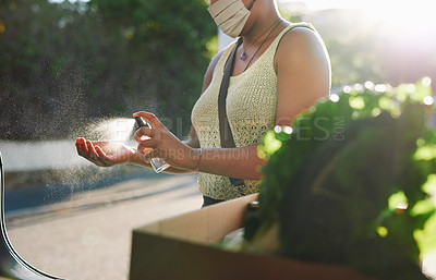 Buy stock photo Cropped shot of a woman wearing a mask and sanitising her hands after shopping for groceries