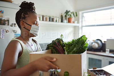 Buy stock photo Shot of a young woman wearing a mask and unpacking her groceries in the kitchen at home