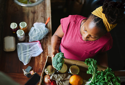 Buy stock photo High angle shot of a young woman unpacking her groceries in the kitchen at home