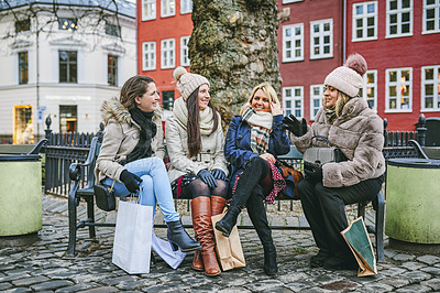 Buy stock photo Shot of a group of young women taking a break while shopping in the city