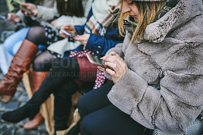 Buy stock photo Shot of a group of young women using their smartphones while out in the city