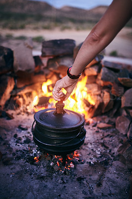 Buy stock photo Cropped shot of a woman cooking traditional South African food by campfire outdoors