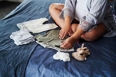 Buy stock photo Shot of a pregnant woman looking at baby clothes while sitting on her bed
