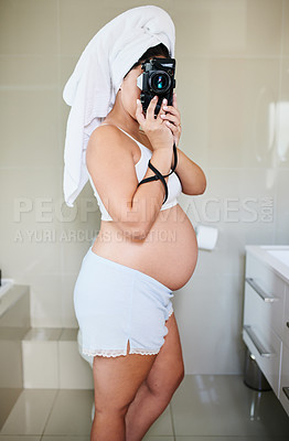 Buy stock photo Shot of a pregnant woman holding up a camera while standing in the bathroom at home