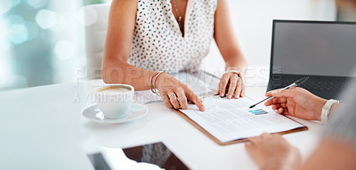 Buy stock photo Closeup shot of two unrecognisable businesspeople going through paperwork together in an office