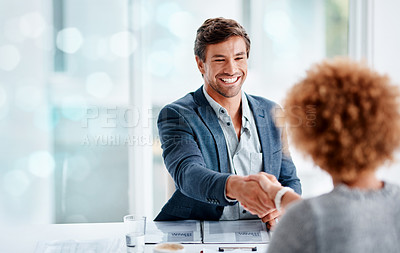Buy stock photo Shot of a young businessman shaking hands with a woman in an office