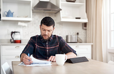 Buy stock photo Shot of a young man using a digital tablet while going over his finances at home