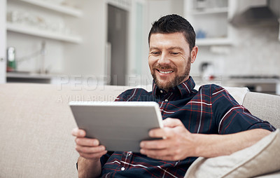 Buy stock photo Shot of a young man using a digital tablet on the sofa at home