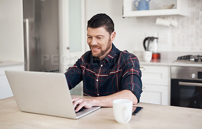 Buy stock photo Shot of a young man using a laptop and having coffee in his kitchen at home