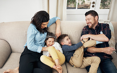 Buy stock photo Shot of a happy family spending quality time together on the sofa at home