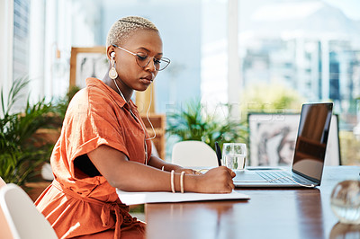 Buy stock photo Shot of a young businesswoman wearing earphones while writing notes in an office