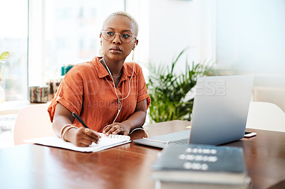 Buy stock photo Shot of a young businesswoman wearing earphones and looking thoughtful while writing notes in an office