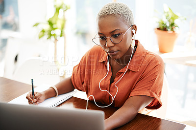 Buy stock photo Shot of a young businesswoman wearing earphones while writing notes and using a laptop in an office